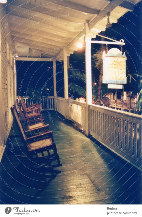 rocking chair Subdued colour Evening Night Artificial light Long exposure Deserted Terrace Serene Patient Calm Key West Florida Rocking chair Exterior shot