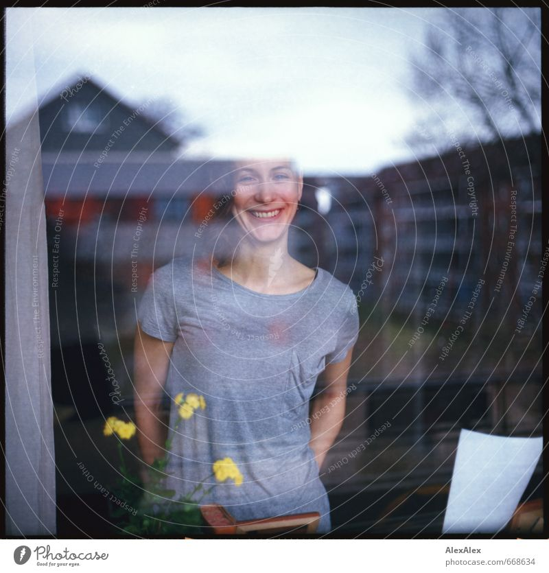 analogue portrait of a young, smiling woman behind a window pane Young woman Youth (Young adults) Head pit 18 - 30 years Adults Flower Apartment house