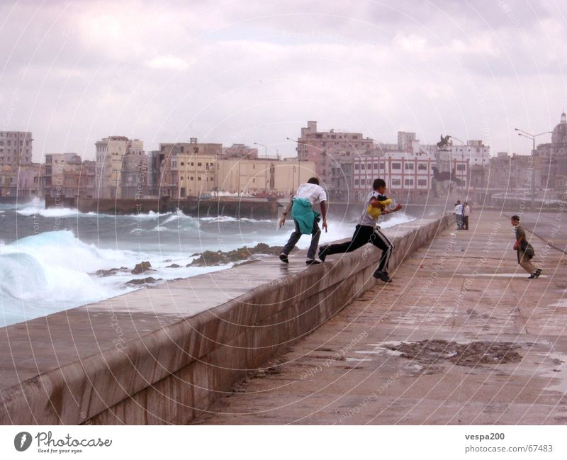 children at malecon Cuba Ruin Ocean Atlantic Ocean Clouds Child Playing Leisure and hobbies Jump Waves Momentum White crest Effervescent Pothole Wall (barrier)