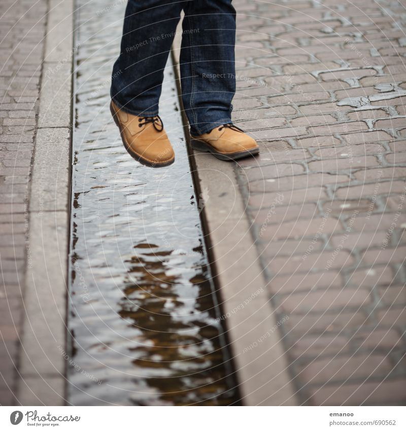 Human being Man City Adults Jump Feet Footwear Walking Hiking Places Wet Trip Jeans Barrier Landmark Downtown