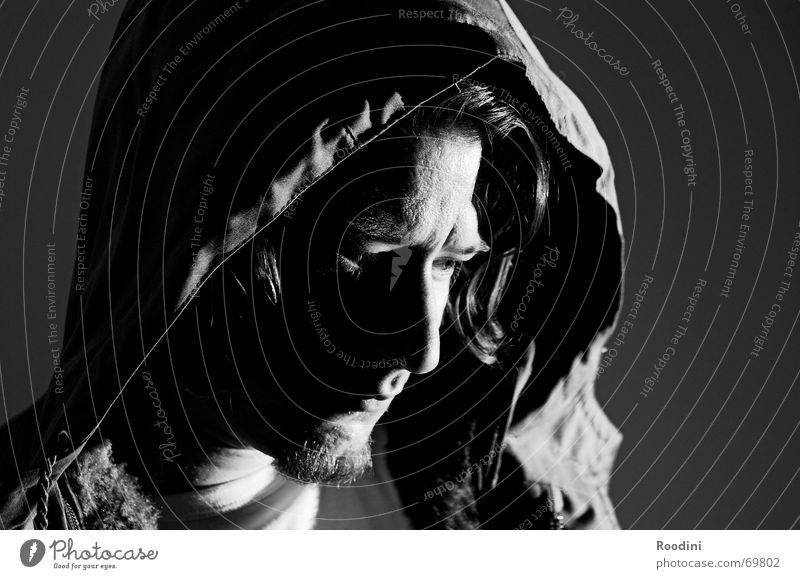 Looking down Man Portrait photograph Dark Hooded (clothing) Objective Thought Think Facial hair Parka Human being Eyes Face Black & white photo Observe