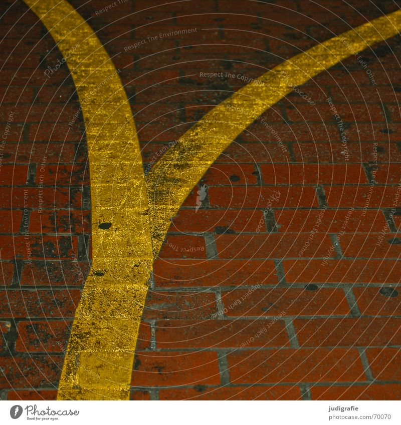 Yellow Street Lanes & trails Line Orange Dirty Signs and labeling Floor covering Letters (alphabet) Tracks Brick Typography Direction Seam Paving stone Swing