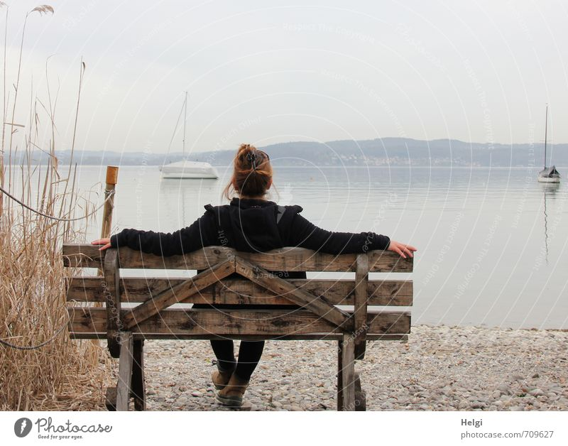 Rear view of a woman with pinned up brunette hair and dark jacket sitting on a wooden bench and looking at a lake in the fog Well-being Relaxation Calm
