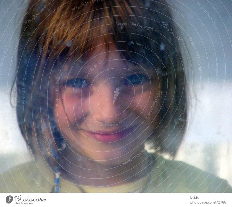 Cute, sweet, cute, smiling, little, dreamy, sweet, sweet girl with pony, looks cheekily, through a dirty pane of glass into the camera and observes, curious, his counterpart. The window is smeared with dirt and drops.