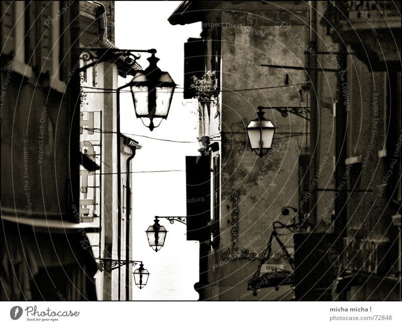 A touch of the Middle Ages Alley Italy Lake Garda Lamp Facade Narrow Light Window Sun blind Medieval times Old yesterday striped Black & white photo