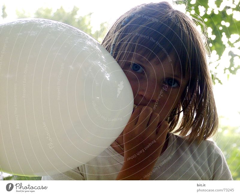 Thoughtful, dreamy, sweet girl with a white balloon in her hand in the garden, looks into the camera. Dear birthday girl outside in the nature is happy about a gift balloon for her party, holds it tight and puts it in her mouth.