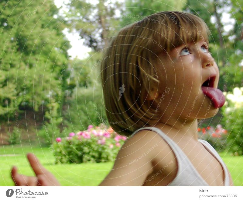 Funny, funny, cheerful, happy, funny blonde girl outside in the garden, looks up and sticks out her red tongue. Little joker is fooling around, fun with twisted eyes in nature, in the park with flowers and trees.