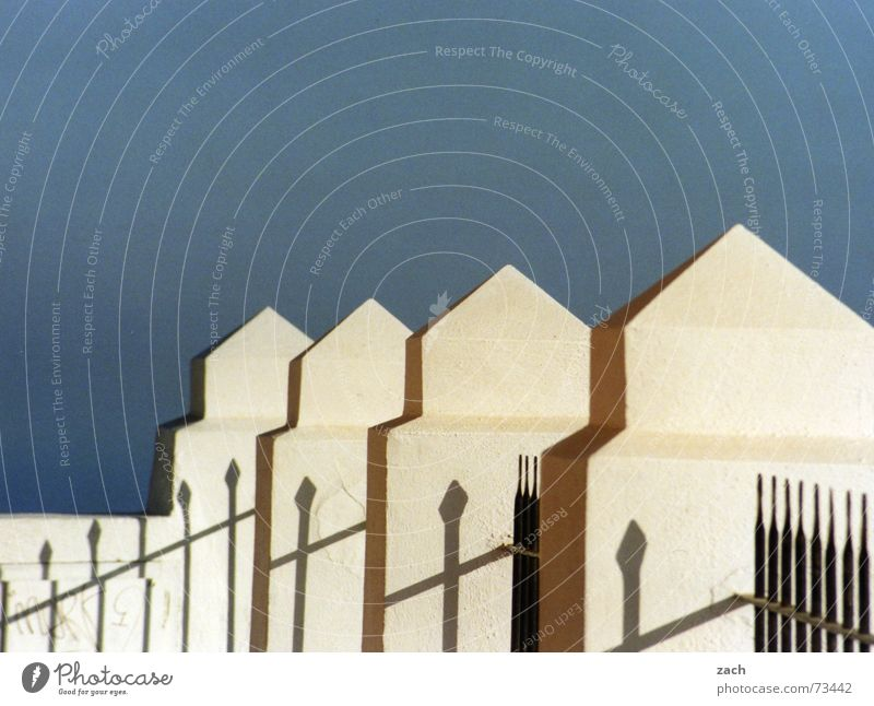 jagged Fence Beaded Behind one another Greece Diagonal Wall (barrier) Border Santorini Detail Europe Obscure Sky Blue Prongs Treetop Shadow Row Perspective
