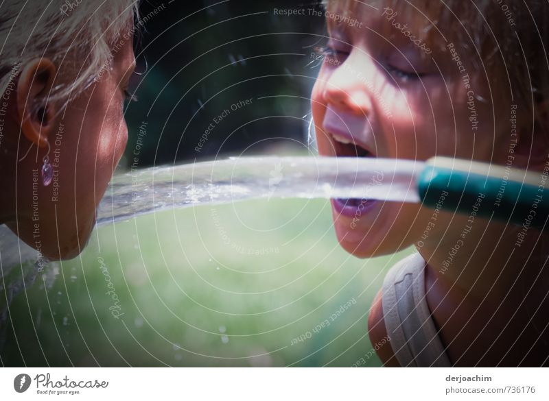 two quench. Two girls are drinking water from a hose that is streaming out. One on the left the other on the right. Drinking Water hose Joy Healthy Life Girl