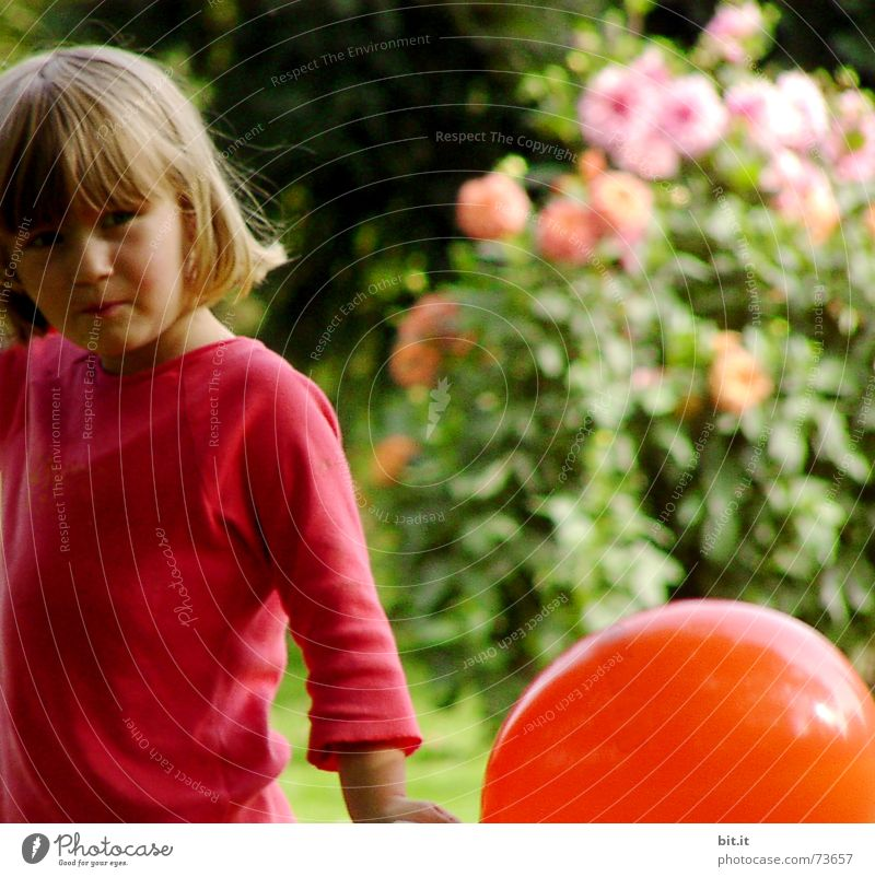 Blonde, sweet girl is standing with a red balloon in her hand in the garden in front of pink flowers in full bloom. Birthday child outside in the nature is happy about the balloon for her party.