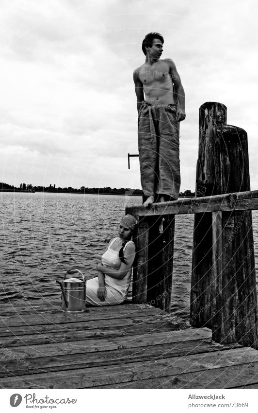 Hans looks in the air Misunderstand Footbridge Wood Man Woman Black Bad weather Clouds Relationship Vantage point Exterior shot Pick up water Watering can