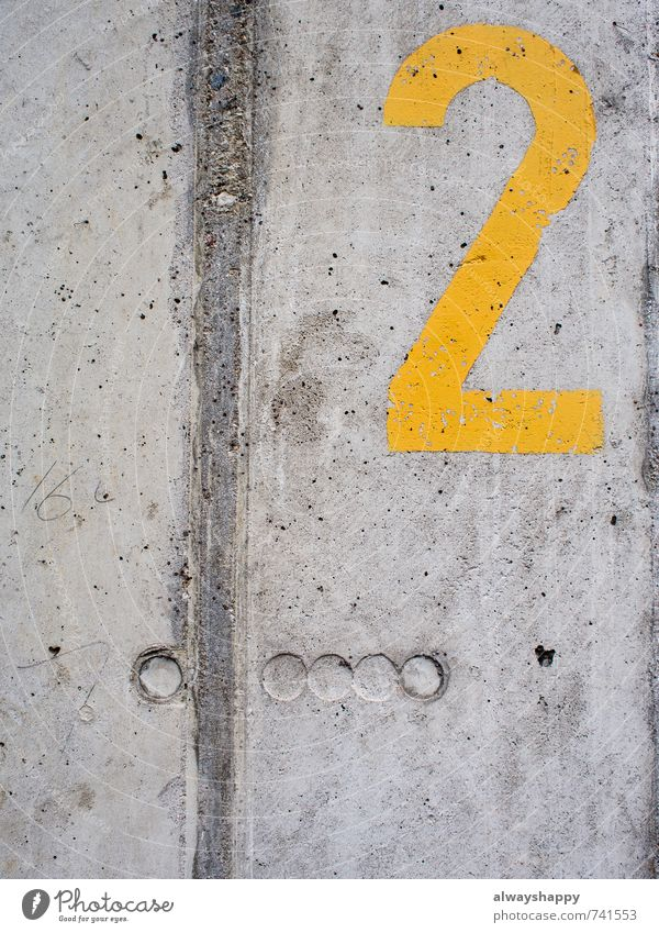 Winners of hearts Style Design Wall (barrier) Wall (building) Concrete Digits and numbers Authentic Cold Broken Yellow Gray 2 two stencil Colour photo
