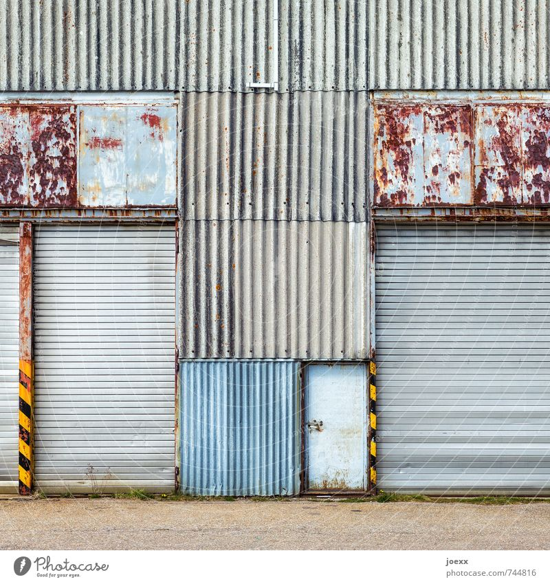 Portal closed Facade Door Gate Metal Old Hideous Retro Blue Brown Yellow Gray Black Transience Corrugated iron wall Line Rust Patina Colour photo Subdued colour