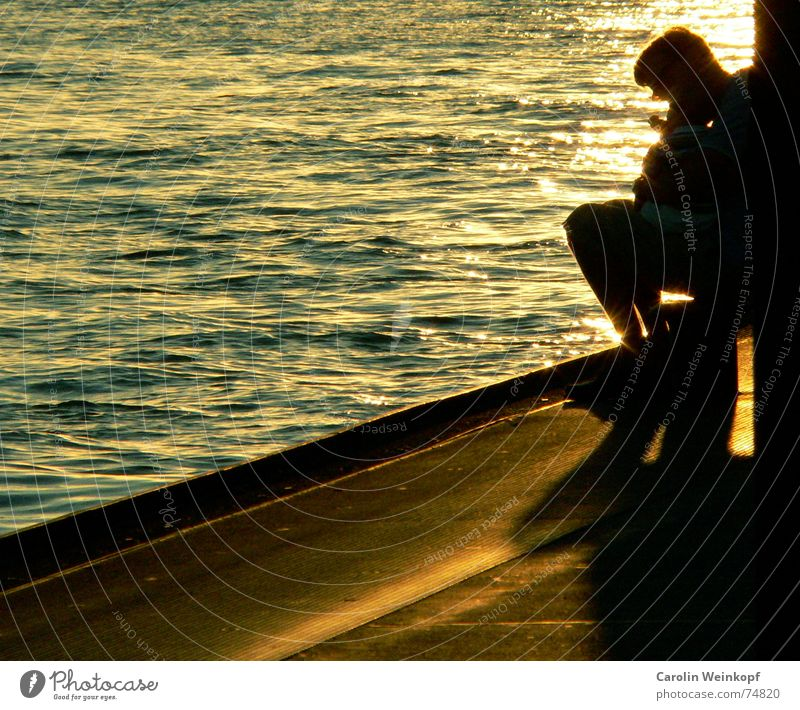 Father and son Light Waves Man Sunset Dusk Harbour Evening Life Water Shadow Jetty Edge Copy Space left Mole Back-light Warm light Sit Silhouette Ambience