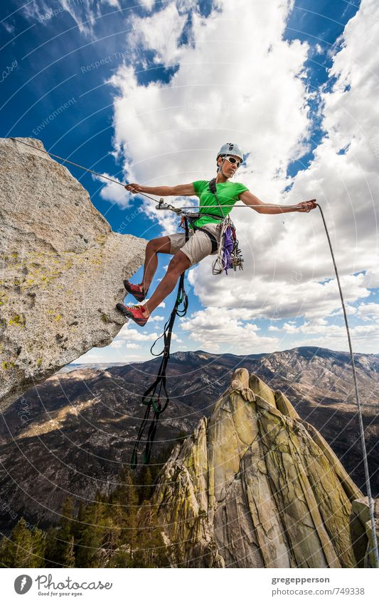 Climber rappels over the edge. Life Adventure Climbing Mountaineering Success 1 Human being 30 - 45 years Adults Clouds Helmet Self-confident Brave