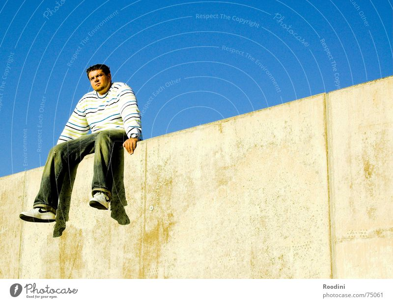On the wall, on the lookout... Wall (barrier) Man Relaxation Break Sky blue Far-off places Jump Sweater Dangle Summer Waiting room Wall (building) Border