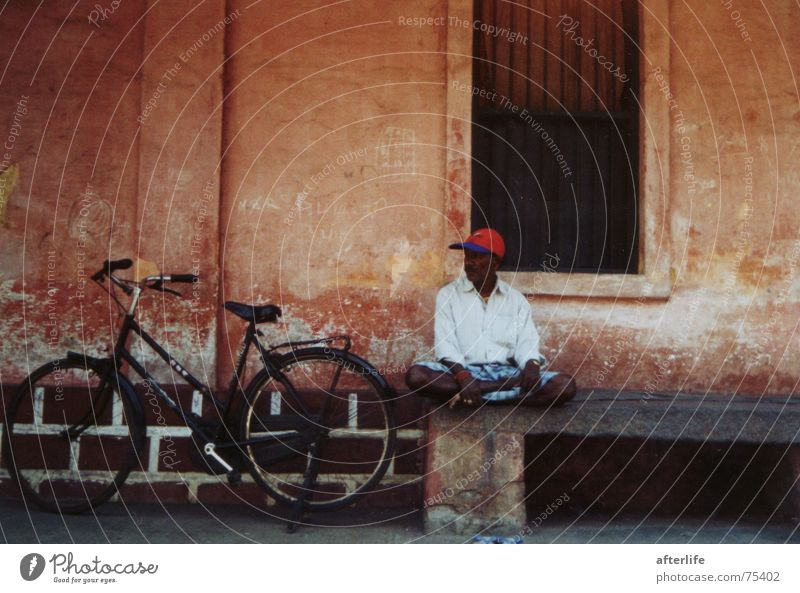 indian dreams pondichery in a small street in the shade a man relaxes beautiful indian colonialhouse-colours his red hat beautiful bycicle