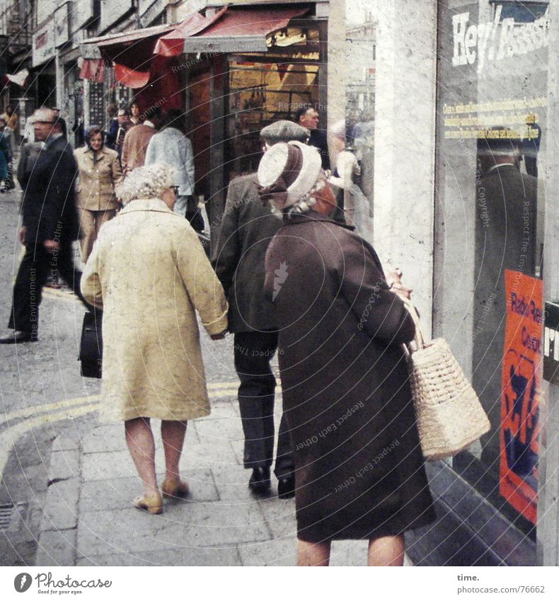 Human being Old Street Shopping Reading To go for a walk Advertising Store premises Lady Hat Paper bag England Amazed Shop window Bag Hold hands