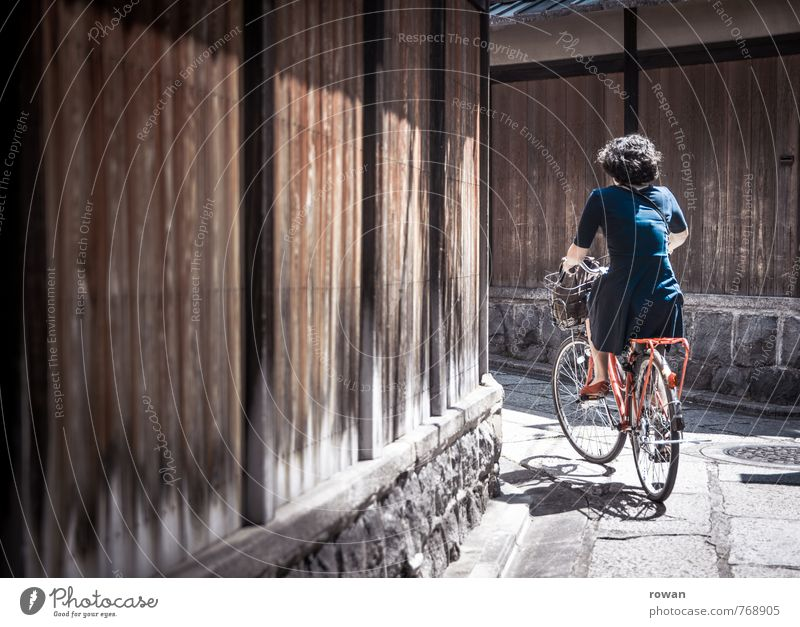 turn Human being Feminine Young woman Youth (Young adults) Woman Adults Cycling Curiosity Warmth Blue Red Cycling tour Bicycle Lanes & trails Trip Turn off