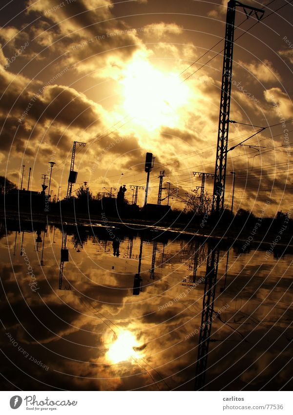 Mirrorun in a puddle Puddle Reflection Back-light Overhead line Electricity Railroad tracks Clouds Dramatic Threat Dark Lateness