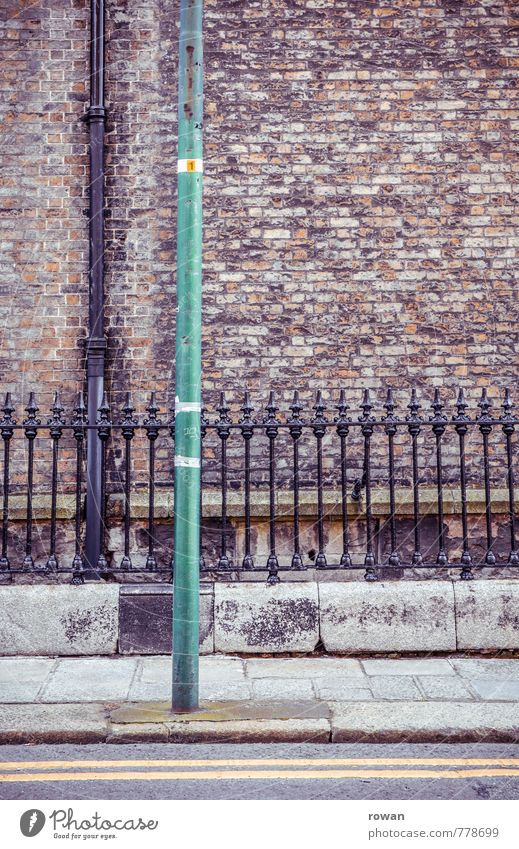 || Wall (barrier) Wall (building) Old Fence Cast iron Downpipe Street Sidewalk England Ireland Brick Brick wall Colour photo Exterior shot Deserted