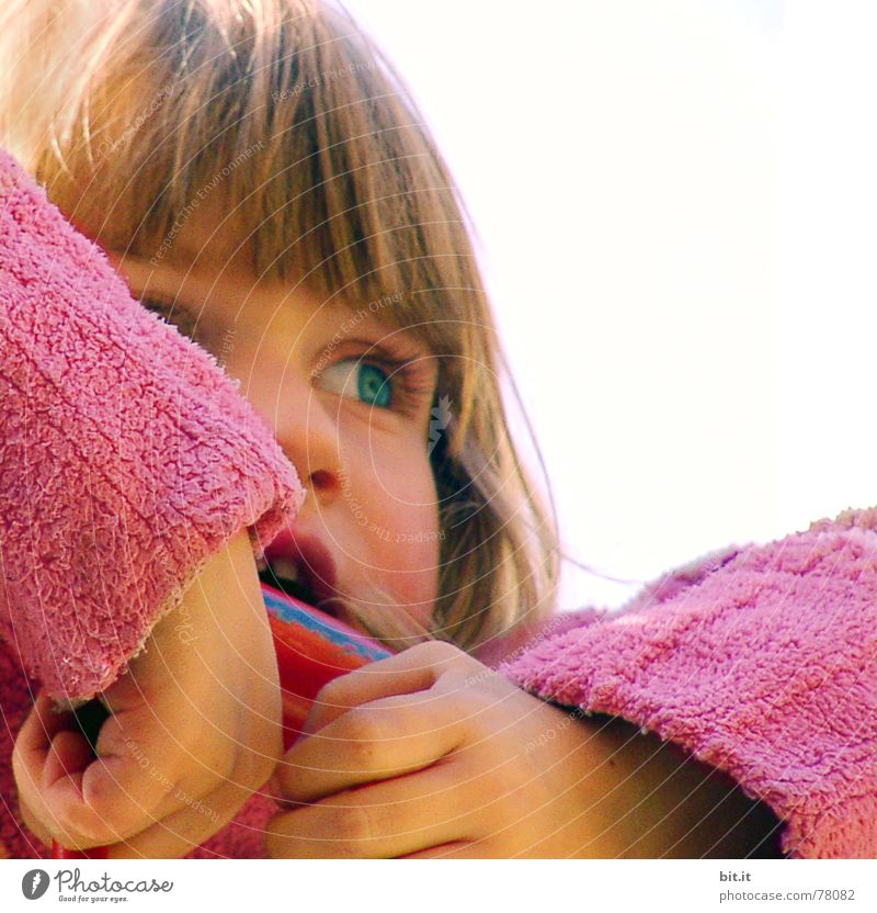 Cute, cute, cute, smiling, little, dreamy, sweet, sweet, blonde girl with pony and sweater in pink, pink observes, curious, interested, cheeky, his surroundings and holds on to the railing from the climbing on the playground.