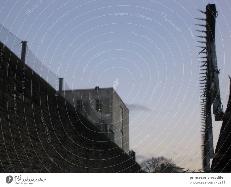 L'heure bleu Barbed wire Wall (barrier) Building Barrier Fence Dark Penitentiary Sky race prison Evening Gloomy