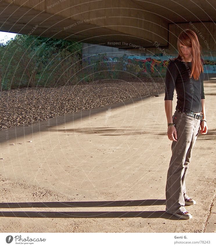 = Human being Woman Young woman Stand Thin Chucks Long-haired Red-haired Dark Shadow Stone Concrete Bushes Appearance Physics Brown Autumn Evening sun Bridge