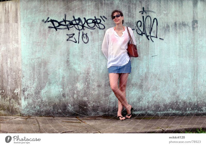 At the wall Mini skirt Blouse Woman Wall (barrier) Sidewalk Dirty Laughter Old Graffiti