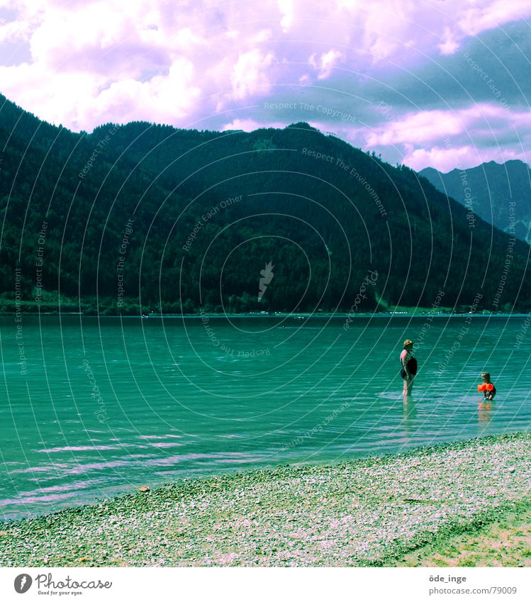 Return to the blue lagoon Lake Swimsuit Water wings Clouds Beach Gravel Austria Woman Mother Child Vacation & Travel Forest Summer Turquoise Wet Stand Crouch