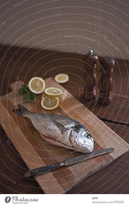 fish Food Fish Dorade Lemon Cooking salt Pepper Nutrition Knives Chopping board Healthy Eating Fresh Delicious Natural Appetite Wooden table Colour photo