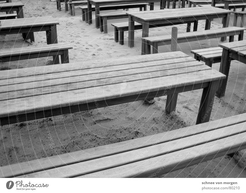 out on the beach Horizontal Wood Table Gray Black Beach Ocean Summer Winter Café Seating Places Arrangement Coast Gastronomy Black & white photo Line Bench Sand