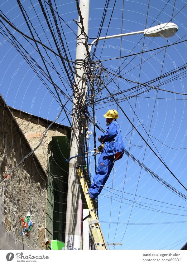 tangled cables Fitter Suva Insecure Helmet Yellow Working clothes Muddled Electricity Bolivia Chaos Electricity pylon Lantern South America Working man Distress