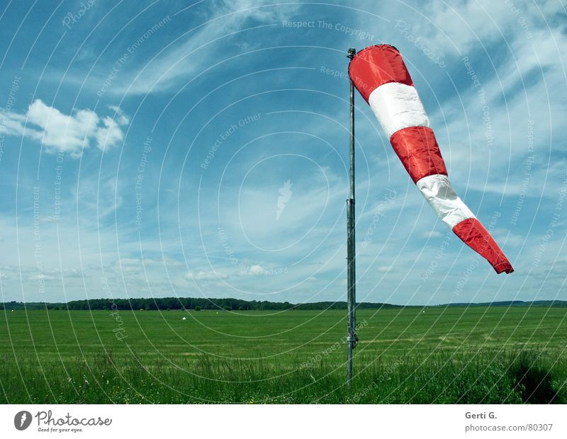 Wind in a bag Windsock Smear Wind direction Red Clouds Sky blue Striped Air Meadow Airfield Grass Flagpole Hang Green Airy Fresh Band of cloud Blue Airspace