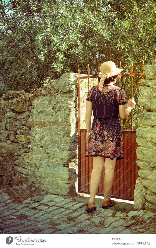 garden gate Human being Feminine Young woman Youth (Young adults) Woman Adults 1 Garden Garden door Entrance Olive tree Dress Hat Wall (barrier) Arise Undo
