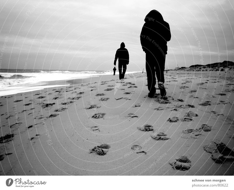 change of perspective Beach Ocean Lake Footprint Black White Gray 3 Man Waves Wind Gale Passion Hooded (clothing) Black & white photo Winter Water Tracks Feet