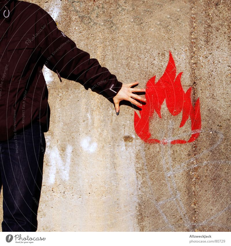flammable Fire alarm Burn Man Wall (building) Wall (barrier) Symbols and metaphors Ignite Hand Red Young man Kindle Blaze Dangerous Graffiti Mural painting
