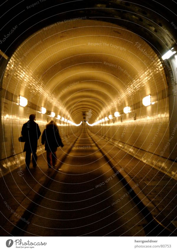 Elbe Tunnel Far-off places Lamp Infinity Traffic lane Pedestrian underpass 2 Yellow Brown Man Woman Oppressive Dark Historic Hamburg Line road toll Couple