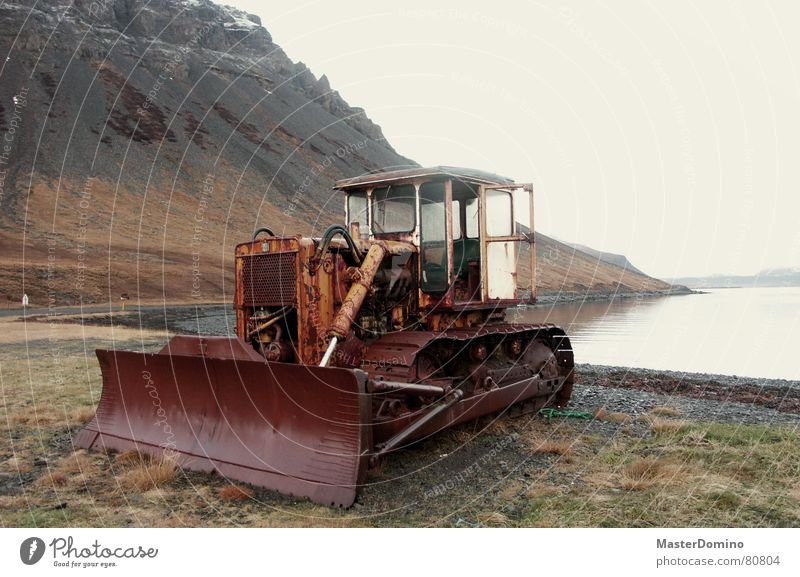 bulldoze the fjord away Bulldozer Lake Exterior shot Westfjord Construction site Past Air Construction worker Rust Machinery Broken Iceland Ocean Grass