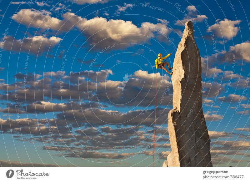 Climber tiptoes on the edge. Human being Clouds Adults Mountain Success Rope Adventure Peak Climbing Fear of heights Brave Balance Mountaineering Self-confident Grasp Cliff
