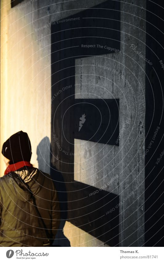 Human being Sun Wall (building) Graffiti Wall (barrier) Going Footwear Walking Concrete Sign To go for a walk Letters (alphabet) Cap Jacket Egg Coat
