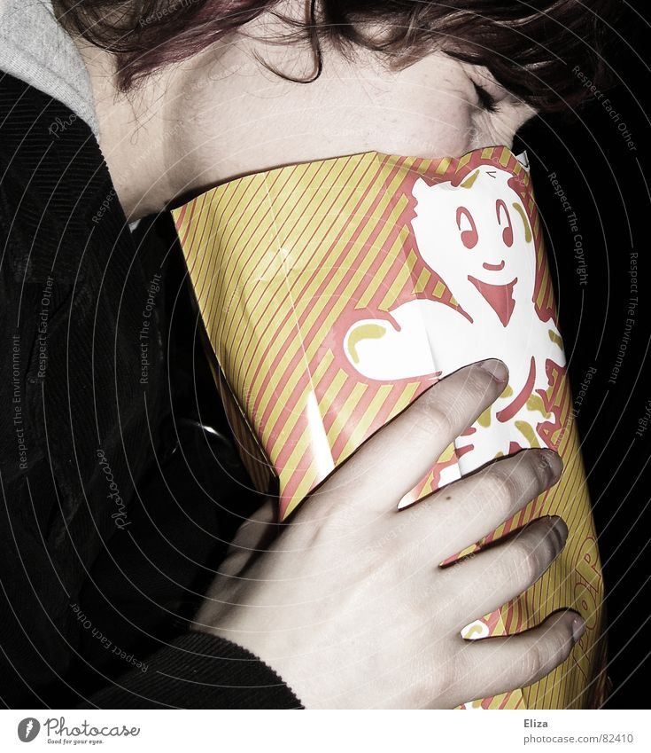 A woman at the movies holding her face in a popcorn bag Cinema Woman Funny Popcorn bag Bad handed over Human being Nausea bunkum Criticism Emotions Food