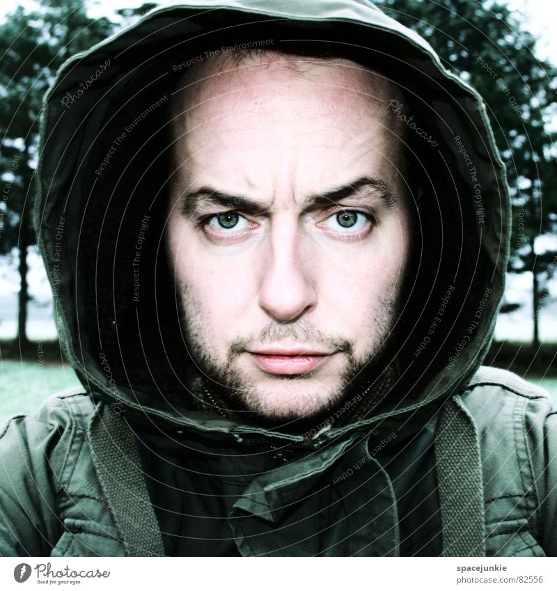 portrait Portrait photograph Hooded (clothing) Jacket Green Tree Fear Facial expression Facial hair Face Skin color Concern Facial colour Glade Young man Fix