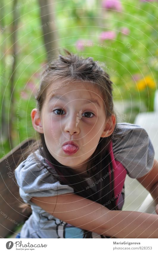 Smiling girl sticks out his tongue - a Royalty Free Stock
