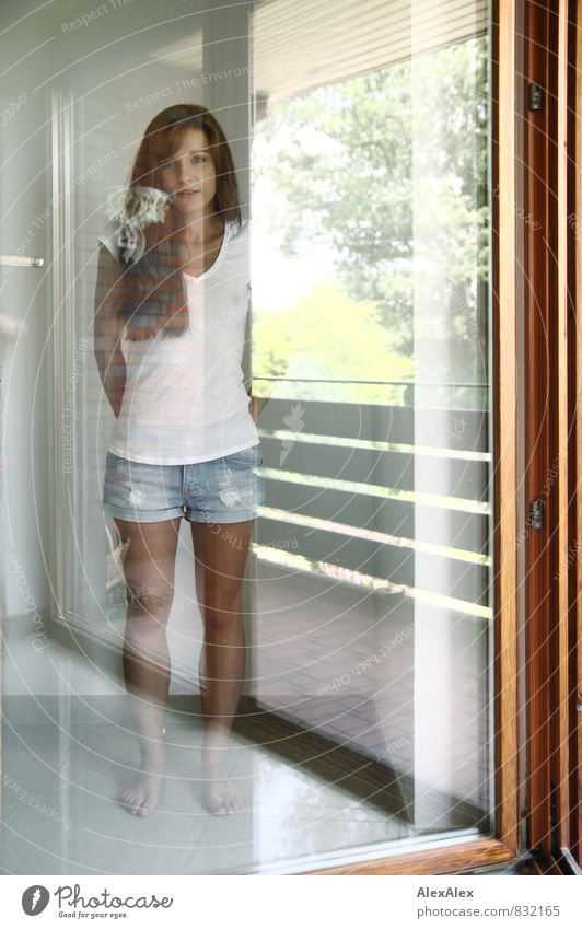 glazed Young woman Youth (Young adults) Legs 18 - 30 years Adults Glass door Window pane Door Balcony T-shirt Hot pants Barefoot Brunette Long-haired Observe