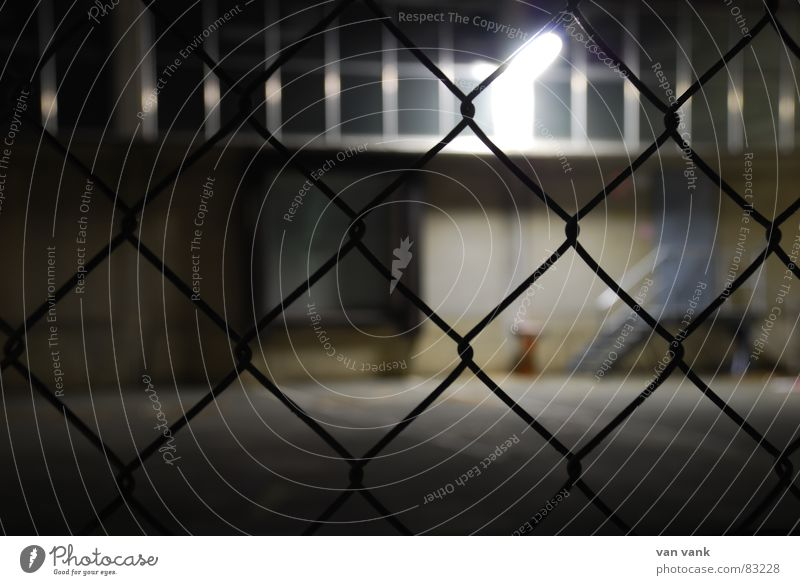 cross-linked Grating Fence Closed Light Lamp Exposure Asphalt Wire Wire netting Window Night Dark Cold Ashtray Loneliness Grief Wall (building) Wall (barrier)