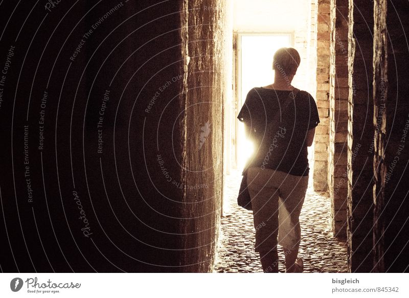 into the light Feminine Woman Adults 1 Human being House (Residential Structure) Wall (barrier) Wall (building) Corridor Cobblestones Stone Going Brown Yellow