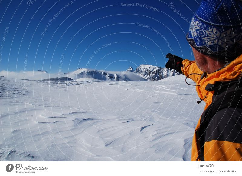 The mountain guide Gloves Cap Cold Mountain guide Slowly Jacket Austria Winter Mountaineering Snow Blue sky Orange Freedom Nature Wind Happy Exterior shot