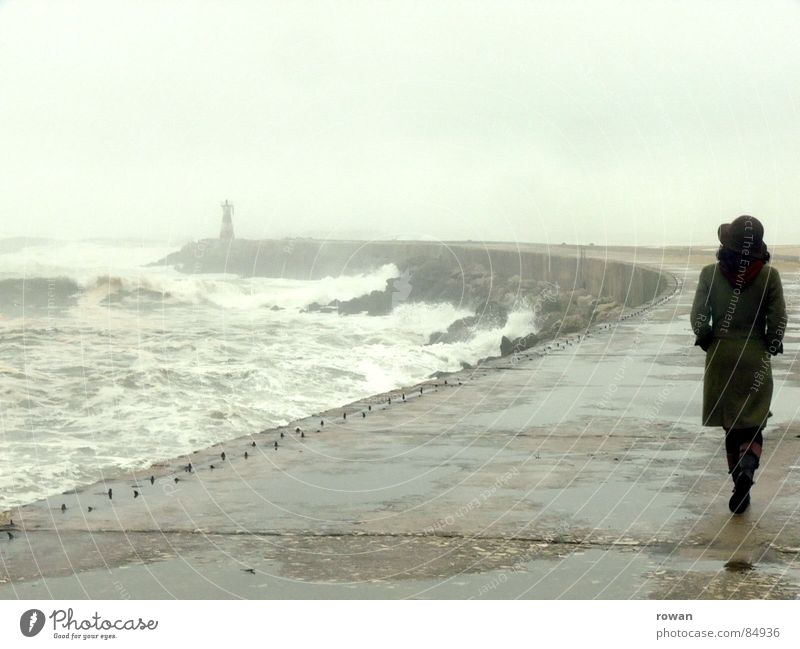 Walk by the sea I Inundated Lake Woman Ocean Waves Lighthouse White crest Fog Puddle Coat Green Going To go for a walk Movement Agitated Gale Wet Cold Gray