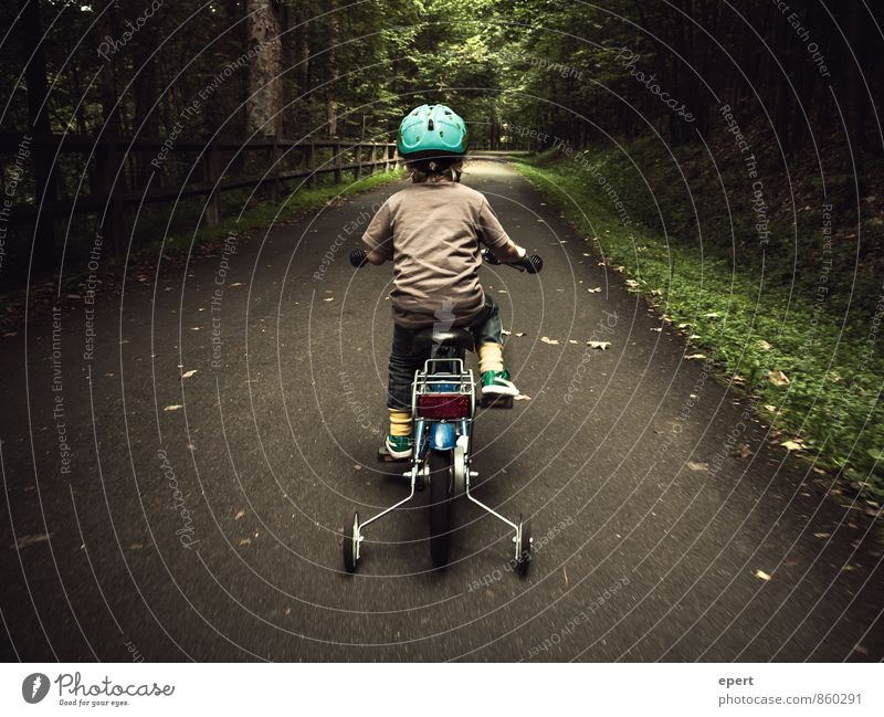 A little man drives in the woods Leisure and hobbies Cycling Child 1 Human being Forest Lanes & trails Bicycle Helmet support wheels Movement Driving Cute Brave